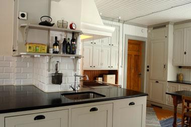 Snickeri Tallkottens visningskök i Torsåker, vitt kök med svarta bänkskivor